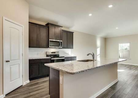 Kitchen with brown cabinets and stainless steel appliances open to the dining room.