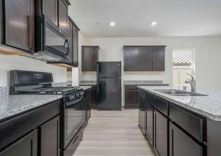The Del Mar floor plan's kitchen with an island, brown cabinets, recessed lighting, black appliances and vinyl wood flooring.