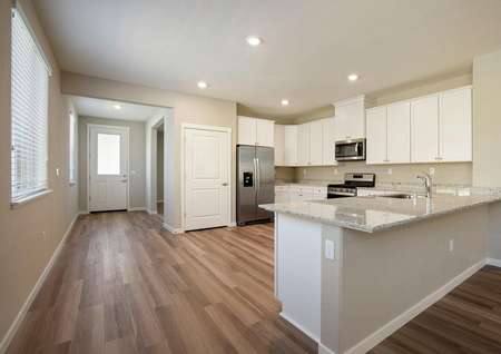 The kitchen is open to the foyer in this home.