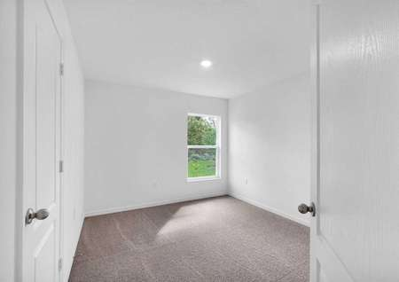 The entrance of a guest bedroom, its spacious closet and a window.