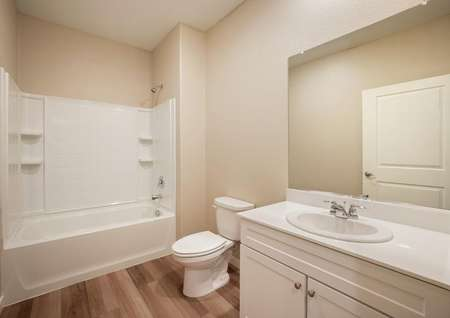 Secondary bathroom with a white vanity.