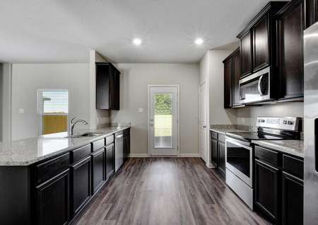 Carson kitchen with granite counters, wood flooring, and door to backyard with glass insert