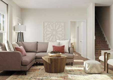 Rendering of the   living room in the Driftwood with a large window, tan walls and carpeted   flooring. The room is decorated with a large sectional, two white armchairs   and a round coffee table.