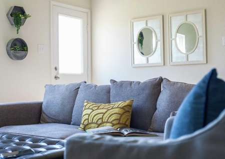 Driftwood model home stages with blueish grey couch that has a green and brown pillow on it and two framed mirrors hanging on the wall in the background