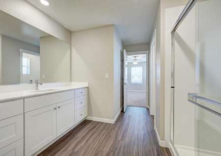 The master bathroom in the Loomis floor plan with wood-like floors, a walk-in shower and cultured marble countertops.