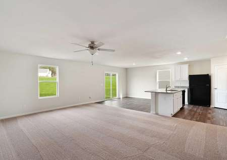 Camden open plan interior with brown carpet family room, tiled kitchen, and white cabinetry