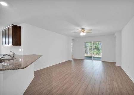 Angle view of kitchen with granite countertops overlooking family room with sliding door.