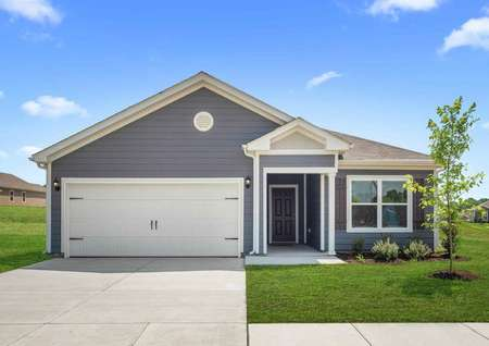The Blanco model home'sexterior consists of grey siding with white trim, white 2 car garage, shingle roofing, shutters on the front window and landscaped front yard