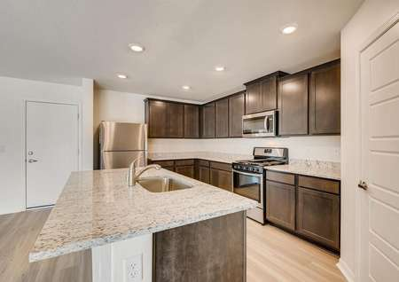 Granite countertops, stainless steel appliances and brown cabinets in the home's kitchen.