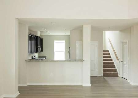 The Mid Atlantic Newport side view of kitchen showing a granite bar and staircase on the right side.