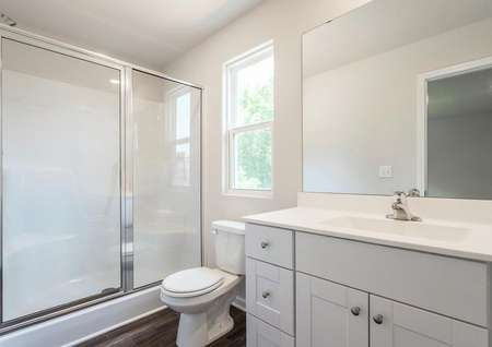 Gorgeous bathroom with white countertops and a walk-in shower.