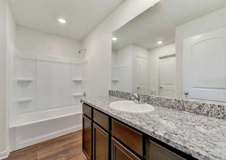 Frio bathroom with granite counters, white fixtures, and bath/tub combo unit