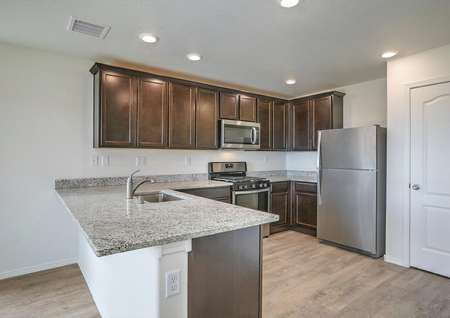 Stunning kitchen with stainless appliances, granite countertops and wood-style flooring.