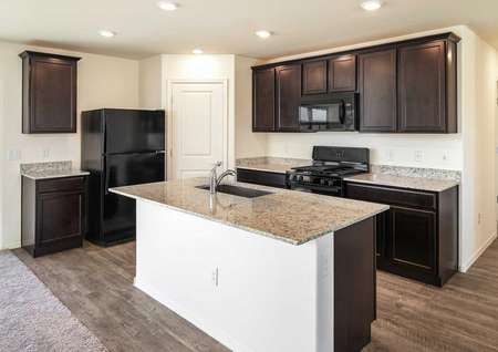The Crescent floor plan kitchen shown with vinyl wood floors and black appliances.