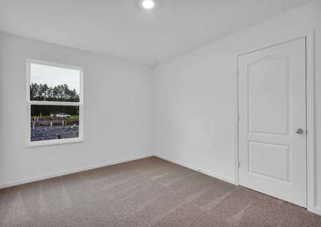 A single hung windowand flush lighting in the carpeted spare bedroom of the St. Martin floor plan.