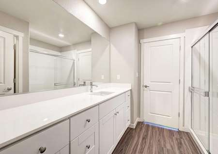 The master bathroom in the Empire floor plan that has white cabinets, recessed lighting and vinyl wood-like flooring.