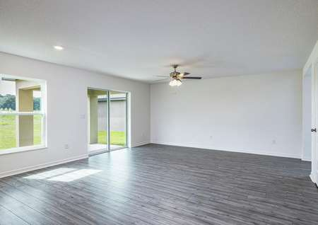 The family room has vinyl plank floors and leads to a covered back patio.