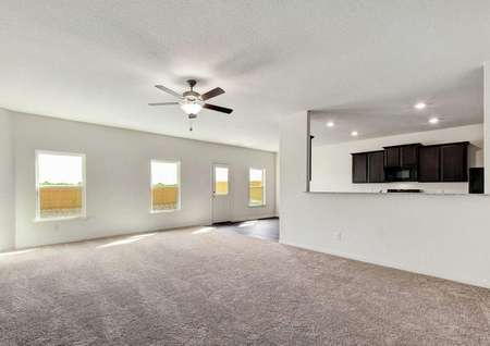 Osage great room with ceiling fan, multiple backyard windows, and brown carpeted floors