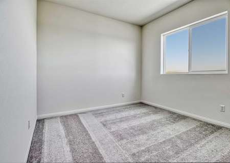 A spare bedroom in the Sunflower floor plan with a window, brown carpet, white baseboards and white walls.