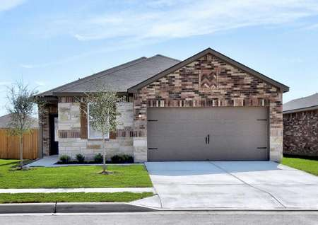 Jasper single-family home with two car garage, brown brick work, and landscaped front yard
