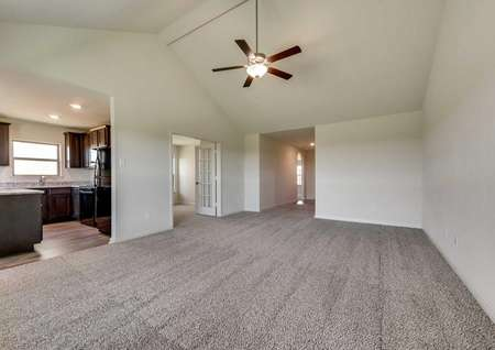 Sabine family room with carpeted floor, vaulted ceiling, and kitchen access