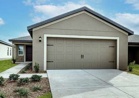 One-story home with a two-car garage, covered entryway and front yard landscaping.