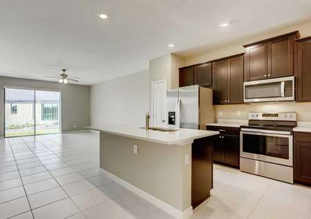 The kitchen and living room in the Patricio model home. Tile flooring, quartz countertops, stainless steel appliances and upgraded cabinetry with crown molding
