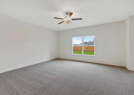 The spacious living room in the Rio model. Carpet flooring a ceiling fan and large window are in the picture
