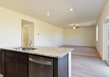 Kitchen with island looks onto dining area and adjacent living room with ceiling fan.