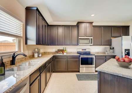 Staged kitchen with dark brown cabinets, stainless appliances, recessed lighting, ceramic tile floor, window with blinds, tall upper cabinets.
