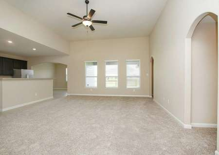 Carpeted living room with three windows, ceiling fan with light, and access to the kitchen in the Leland model