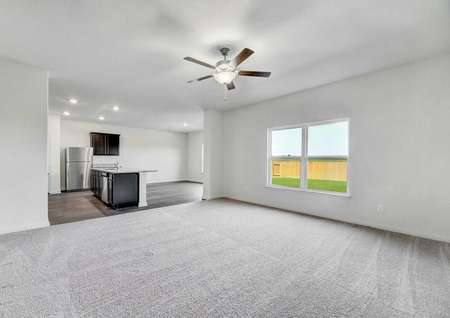 Rio great room with ceiling fan, light gray carpets, and white on white walls