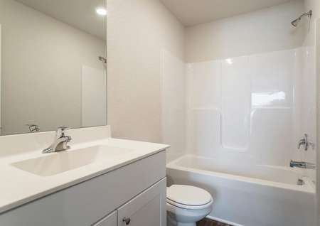 Gorgeous bathroom with white countertops and a dual tub and shower.
