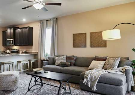 Staged living room with view of kitchen.