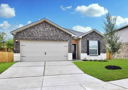 Fannin finished home design with dark brick finish, concrete driveway, and green grass