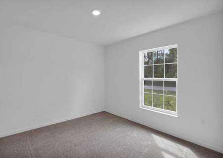 Spacious guest bedroom with a large window that lets in plenty of natural light.
