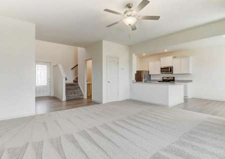 Large living room with carpet and ceiling fan looks toward foyer and staircase. breakfast bar and into kitchen.