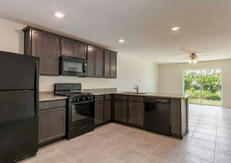 Bahia plan's kitchen withbrowncabinets, all black appliances & a view of the living room with tile living room & kitchen.