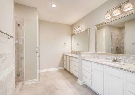 Timberline master retreat bath with two vanities, wall-mounted and ceiling light fixtures, and open glass shower door