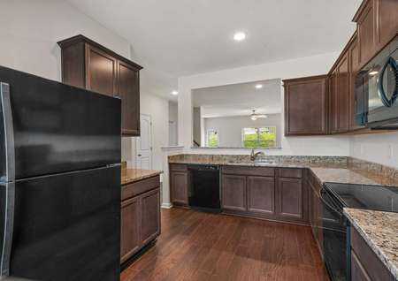 The Driftwood kitchen has wood style vinyl flooring, dark brown crown molded cabinets with recessed lighting, granite countertops, and black appliances