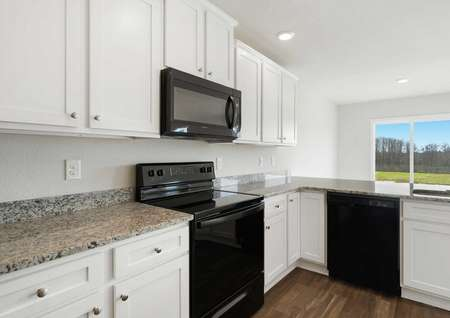 Ashley kitchen with white cabinets, modern appliances, and recessed lighting
