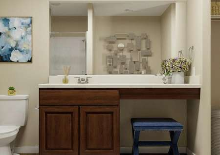 Rendering of the   spacious master bath with brown cabinet vanity flanked by a white toilet and   linen closet.