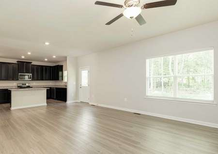 The Mid Atlantic living room with vinyl wood flooring and the kitchen shown in background.