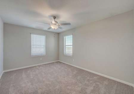 Secondary bedroom in the Loomis floor plan with light brown carpet, tan walls, white baseboards and a ceiling fan.
