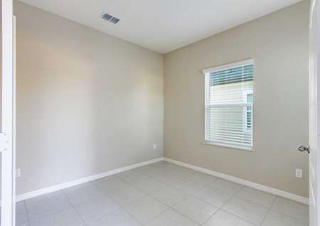 A tile-floored study room in the Mykka floor plan with white baseboards, tan walls and a single window.