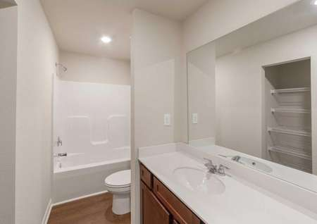 Master bath featuring plenty of countertop space and a linen closet.