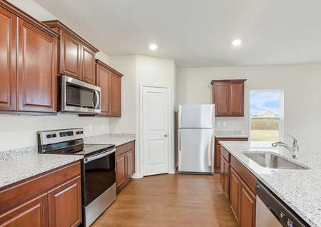 Full view of installed kitchen appliances, granite countertops and upper-wood cabinets.