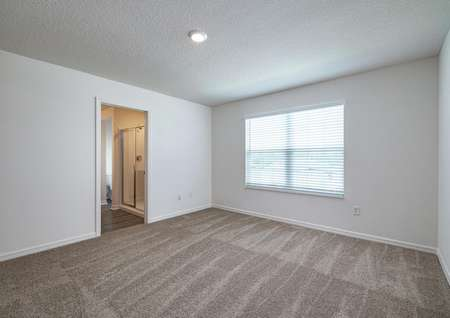 The carpeted master bedroom has one large window and its own full bathroom.