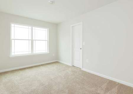 The Mid Atlantic Newport second bedroom shown with carpet and a large window allowing lots of natural lighting.