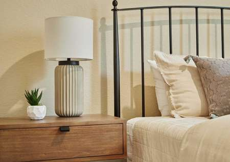 Staged bedroom photo showing a bed with pillows and a bedside table with a lamp and plant.